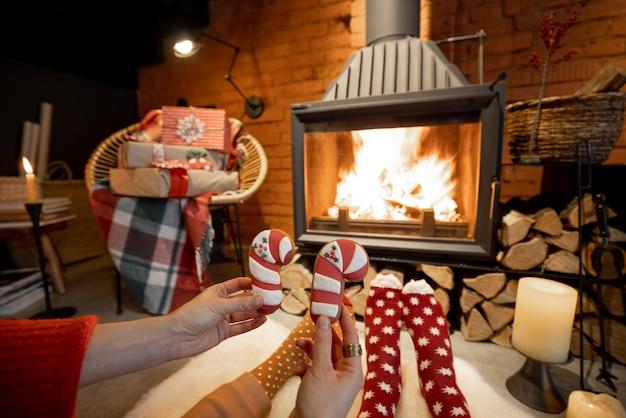 Paar liggend bij de brandende open haard versierd voor de nieuwjaarsvakantie in een gezellig huisinterieur, met kerstkoekjes