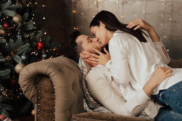 Paar liggend op de bank, is knuffelen en kussen rond de kerstboom thuis.