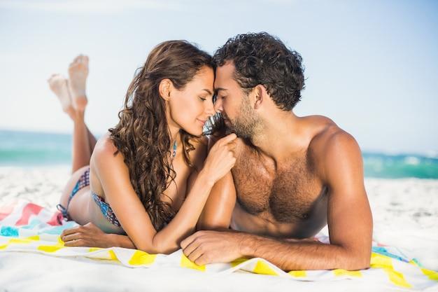 Paar liggend op een handdoek op het strand
