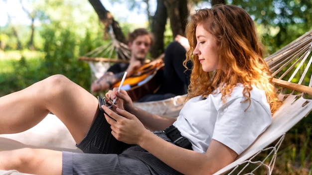 Paar liggend op hangmatten jonge man speelt gitaar terwijl vrouw tablet gebruikt