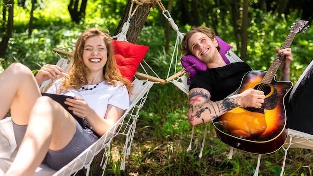 Paar liggend op hangmatten jonge man speelt gitaar