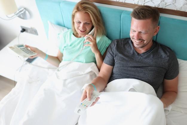 Paar ligt in bed in hotelkamer.