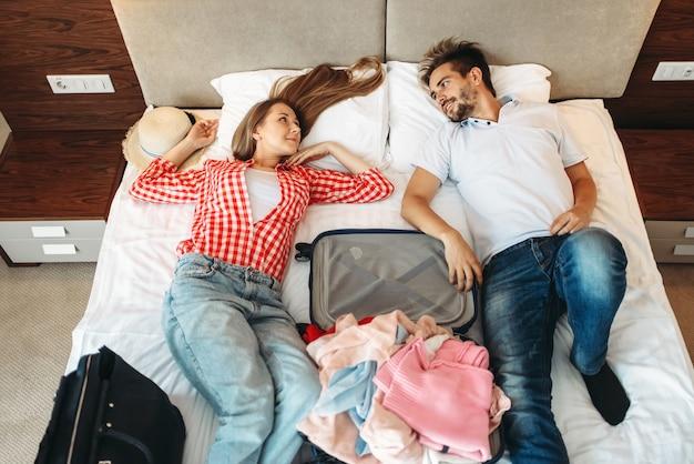 Paar ligt op bed met geopende koffer, bovenaanzicht