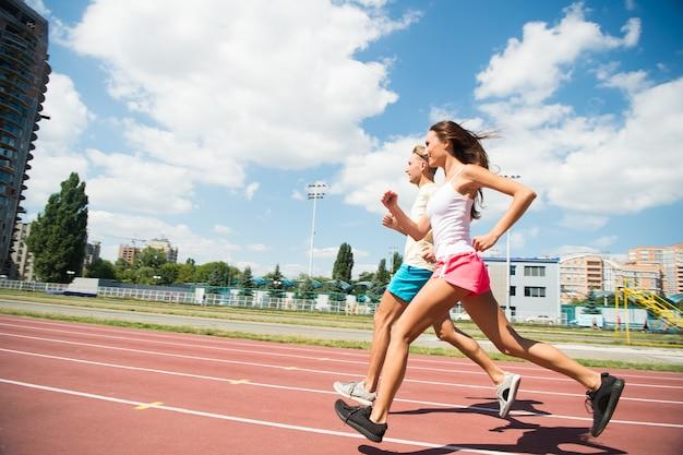 Paar lopers op zonnige buiten. vrouw en man rennen op stadion. activiteit en energie. trainen en trainen op frisse lucht. sportgezondheid en welzijn.
