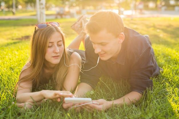 Paar luisteren naar muziek op koptelefoon op het gras
