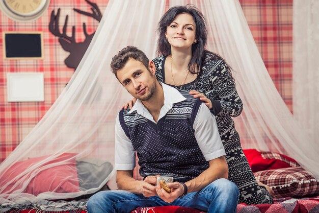 Paar man en vrouw in de slaapkamer thuis thee drinken met koekjes in het rode kerstinterieur