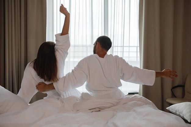 Paar man en vrouw in witte jassen zittend op bed na het wakker worden en zich uitstrekt voor raam in hotelkamer
