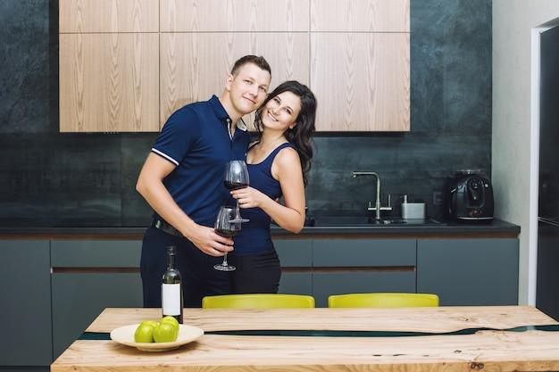 Paar man en vrouw jong mooi en gelukkig in de keuken met winan glazen