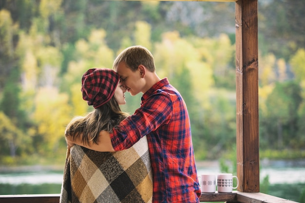 Paar man en vrouw jong mooi gelukkig op de veranda van een houten huis in de natuur met mokken warme dranken