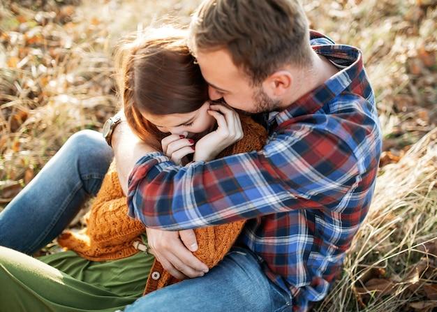 Paar man en vrouw lachen, zittend in een veld buiten, man knuffelen vrouw.