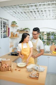 Paar man en vrouw met schorten die plezier hebben tijdens het maken van zelfgemaakte pasta in de keuken thuis