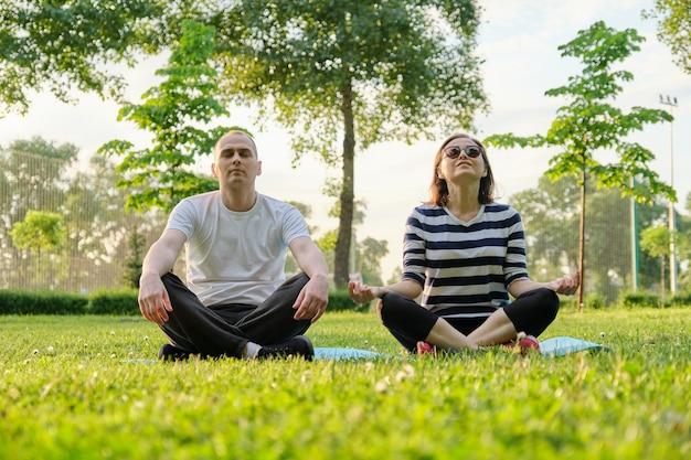 Paar, man en vrouw zitten in het park op mat in lotushouding en mediteren. yoga, fitness, actieve gezonde levensstijl bij mensen van middelbare leeftijd