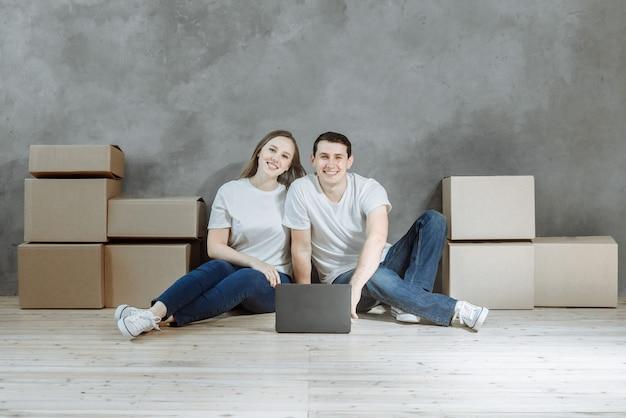 Paar man en vrouw zitten samen met een laptop tussen de kartonnen dozen in een nieuw huis.