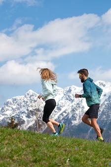 Paar mannelijke en vrouwelijke atleten trainen in de bergen