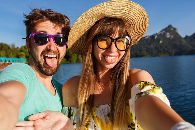 Paar markering selfie in de buurt van geweldig uitzicht op het meer en de bergen, stijlvolle kleding en accessoires dragen. speelse vrolijke sfeer.