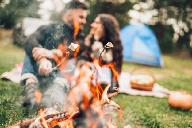 Paar marshmallows roosteren boven het kampvuur