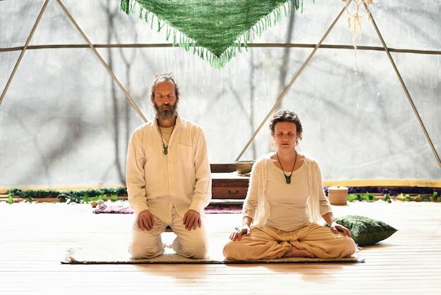 Paar meditatiemeesters in lotushouding in geodetische koepel