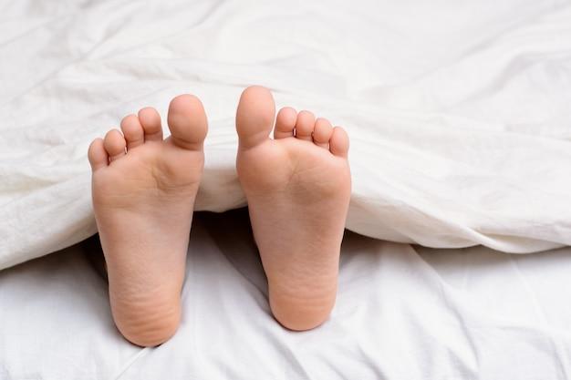 Paar meisje` s voeten in een bed