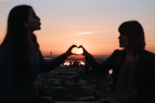 Paar meisjes in de schaduw die liefde vieren bij een zonsondergang