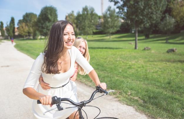 Paar meisjes rijden met fiets in het park