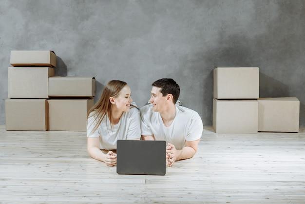 Paar mensen liggend op de vloer van het appartement met dozen en met behulp van een computer, laptop, blij van verhuizing naar een nieuw huis