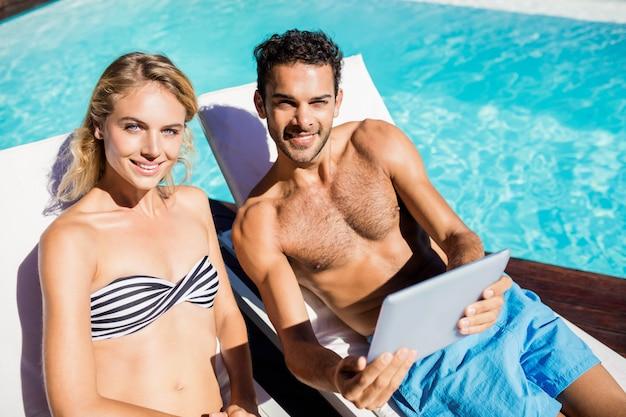 Paar met behulp van tablet op ligstoelen bij het zwembad