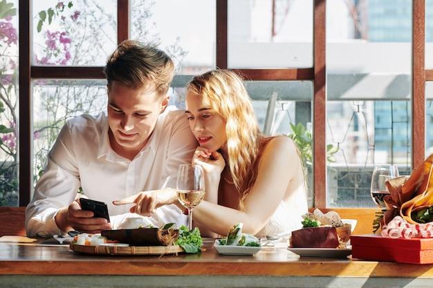 Paar met behulp van telefoon tijdens het diner