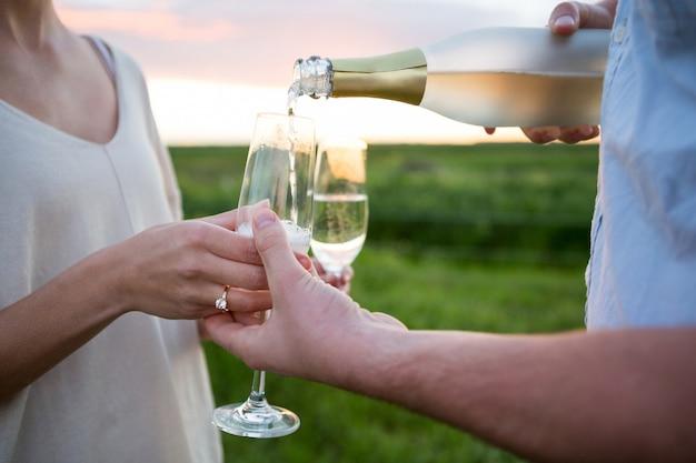 Paar met champagne in veld