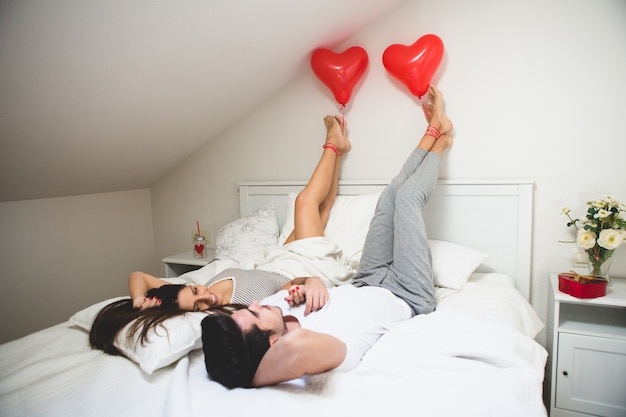 Paar met de voeten op de muur en het houden van een ballon met zijn voet