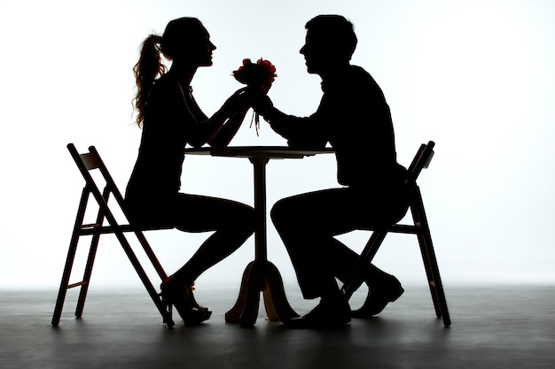 Paar met diner met wijnglas op tafel. silhouetten op witte achtergrond