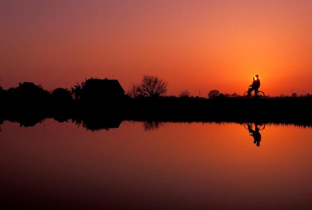 Paar met fiets afgetekend tegen zonsondergang hemel staande op de oever van afgelegen meer