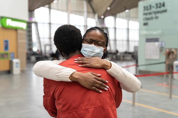Paar met gezichtsmasker knuffelen elkaar binnen de nieuwe normaliteit op luchthaventerminal