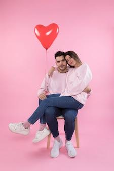 Paar met hartballon die op stoel koestert