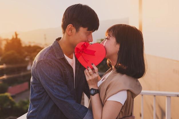 Paar met hun mond bedekt met een hartvormige geschenkdoos