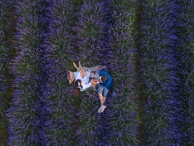 Paar met romantische date picknick bij lavendelveld bovenaanzicht