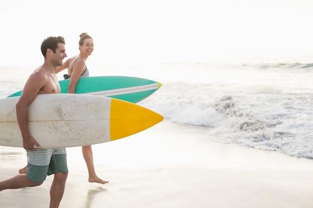 Paar met surfplank die op het strand loopt