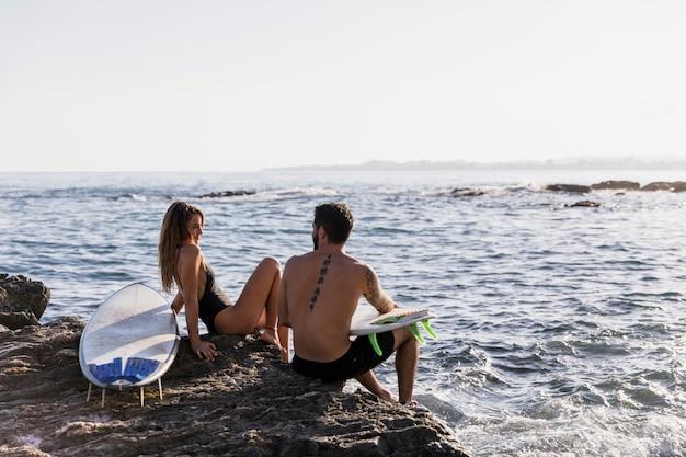 Paar met surfplanken die elkaar op kust bekijken
