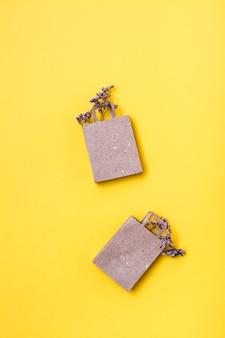 Paar milieuvriendelijke boodschappentassen van ambachtelijk papier met gedroogde bloemen op een gele achtergrond. verkoop van black friday cadeaus. verticale weergave