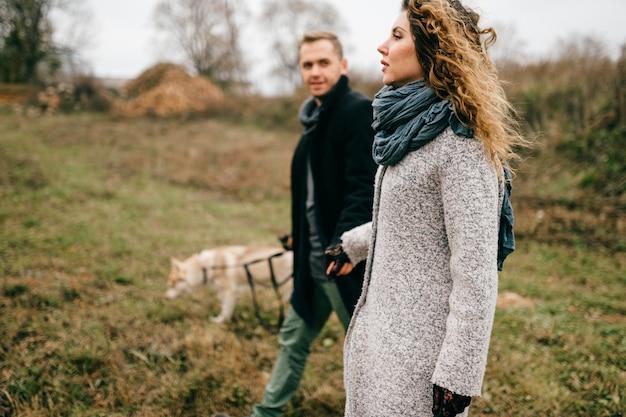 Paar minnaars die met schor puppy openlucht in platteland in de lente lopen. man en vrouw met hun klein harig geliefd binnenlands huisdier die en bij aard in bewolkte dag koesteren rusten.