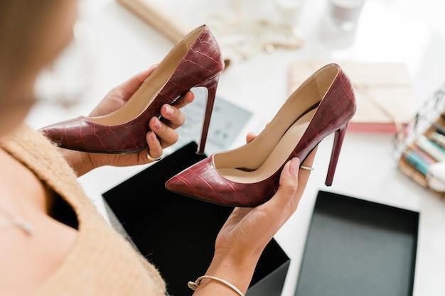 Paar modieuze lederen schoenen met hoge hakken vastgehouden door jonge vrouwelijke klant over open zwarte doos