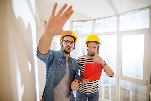 Paar mooie gefocuste jonge ingenieurs met helmen bij het bespreken van de volgende stap.