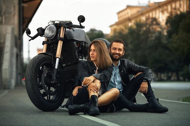 Paar mooie geliefden zitten knuffelen naast een motorfiets