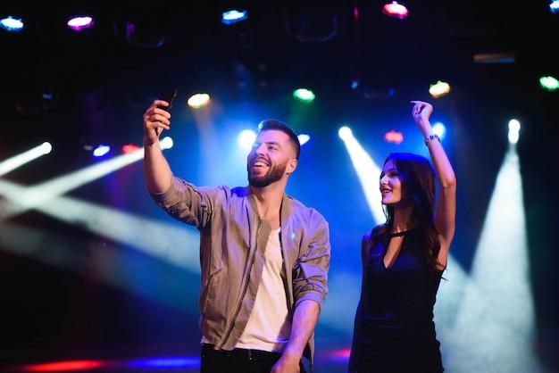 Paar nemen een selfie met een mobiel in de nachtviering