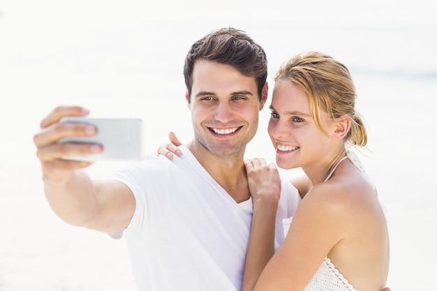 Paar nemen een selfie op het strand