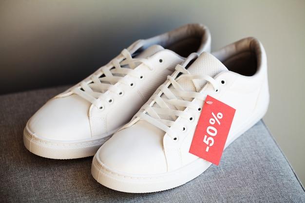 Paar nieuwe stijlvolle witte sneakers met korting op grijs
