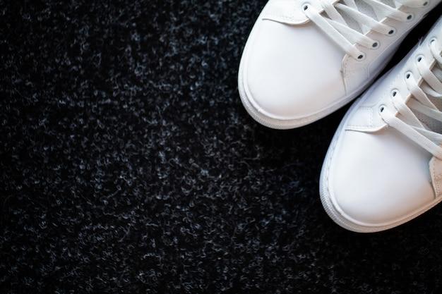 Paar nieuwe stijlvolle witte sneakers op vloer thuis.