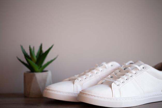 Paar nieuwe stijlvolle witte sneakers op vloer thuis