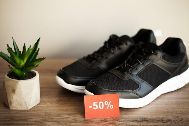 Paar nieuwe stijlvolle zwarte sneakers met korting op grijs