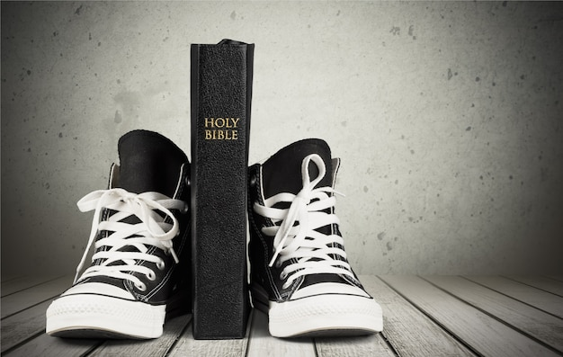 Paar nieuwe zwarte sneakers en holly bible geïsoleerd op de achtergrond.