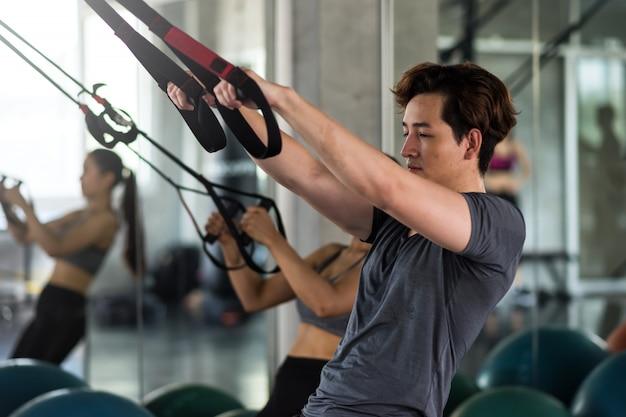 Paar oefenen buikriemen in de sportschool
